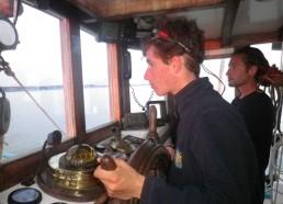 Pierre prend la barre du bateau