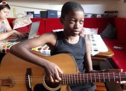 Idrissa s'initiant à la guitare