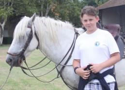 Kylian heureux auprès du cheval blanc