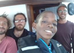 Moha à la barre entouré des marins et du capitaine