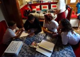 Mathéo et Hugo soutenus par Magalie et Camille à remplir le cahier d'observation maritime